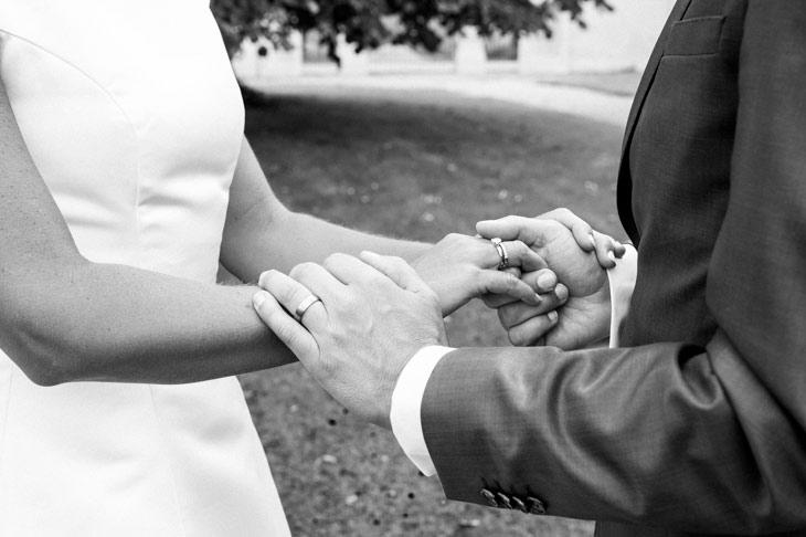 nærbillede af brudepars hænder med vielsesringene