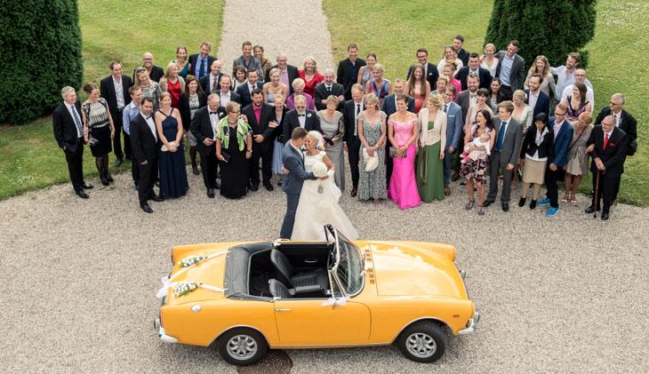 brudepar krammer foran gæster og bryllupsvogn