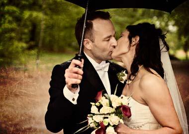 Brudepar der kysser under en paraply