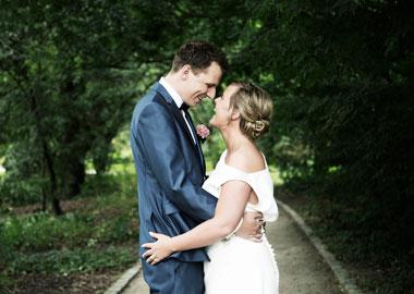 Brudepar der står på skovsti og holder om hinanden
