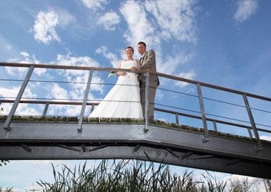 Brudepar der står på en bro