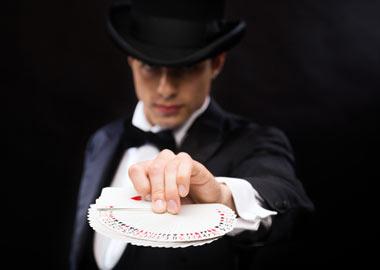 Tryllekunstner der holder en masse kort