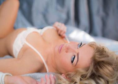 Boudoir billede af kvinde i hvidt undertøj der ligger på ryggen