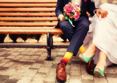 Brud og brudgom i farvestrålende tøj sidder på bænk