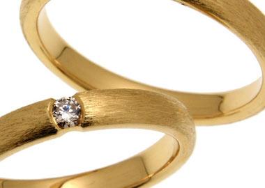 Vielsesringe i guld med ru overflade og en sten i dameringen