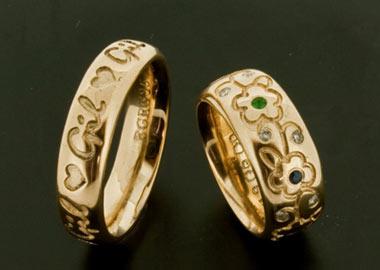Vielsesringe i guld med udskæringer og blomster og sten i forskellige farver på dameringen