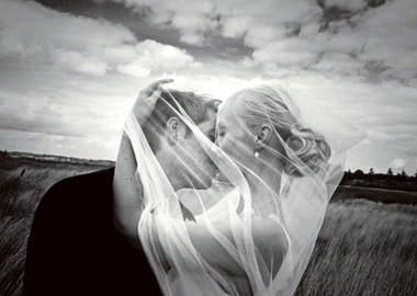 Brudepar der kysser i en kornmark med flagrende slør