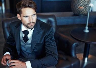 Brudgom i mørkeblå jakke, grå vest og hvid skjorte