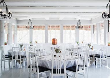 Herthadalen festlokale med runde borde, hvid dug og sprossede ruder