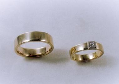 Vielsesringe i guld med skarpe kanter og stor diamant i dameringen