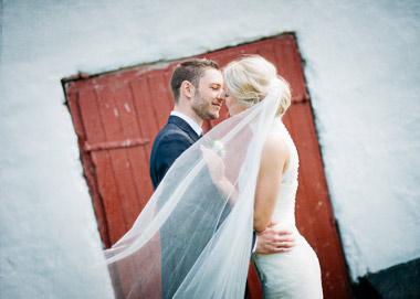 Brudepar der kysser foran rød port