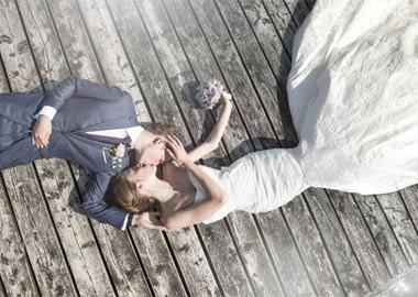 Brudepar der ligger på jorden fotograferet oppefra