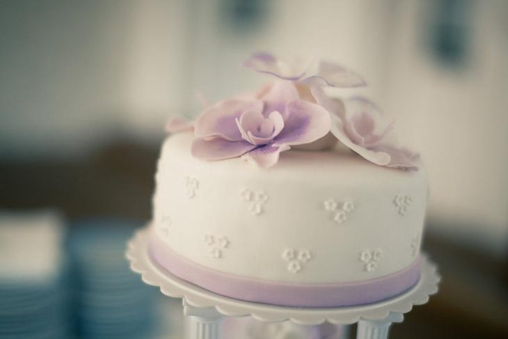 nærbillede af bryllupskage med lilla pynt