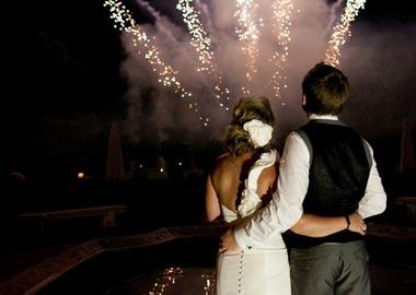 Brudepar der holder om hinanden mens de ser fyrværkeri
