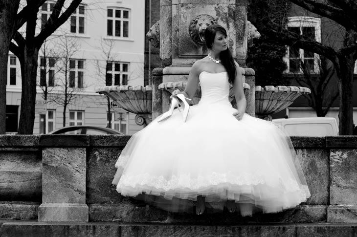 Brud sidder på springvand i stor tyl brudekjole