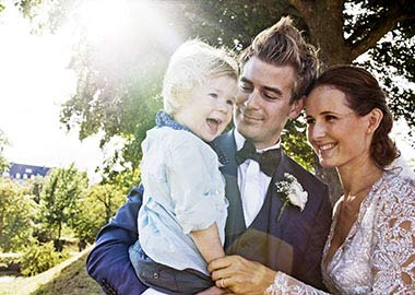 Brudepar der står med deres søn