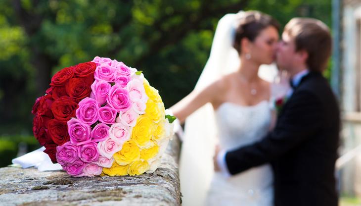 brudepar kysser i forgrunden brudebuket med roser