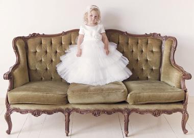 Lille brudepige i hvid kjole der står i sofa