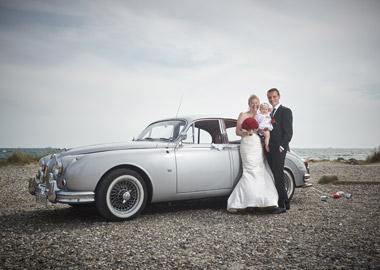 Brudepar der står foran flot ældre bil