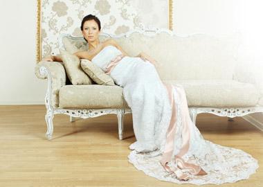 Model i blonde brudekjole med langt slæb og lyserødt bånd