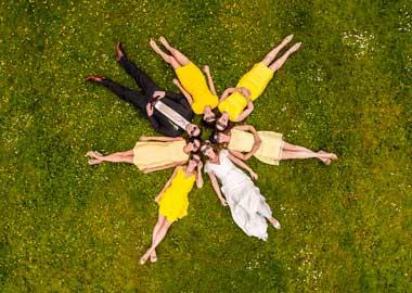 Brudepar fotograferet oppefra ligger på jorden sammen med 5 brudepiger