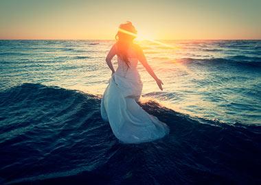 Brud fotograferet på stranden i solnedgang
