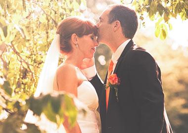 Brudepar der kysser i grønne omgivelser