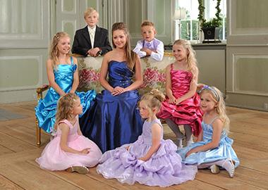 Stor brudepige omgivet af mindre brudebørn i tøj i alle farver