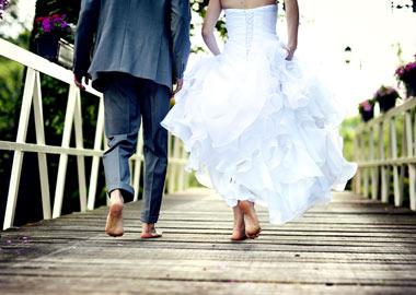 Brudepar der går ved siden af hinanden på træbro i bare fødder