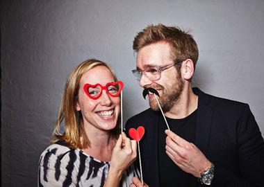 Mand og kvinde med skøre rekvisitter i photobooth