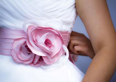 Stor lyserød silkeblomst som bælte på brudekjole