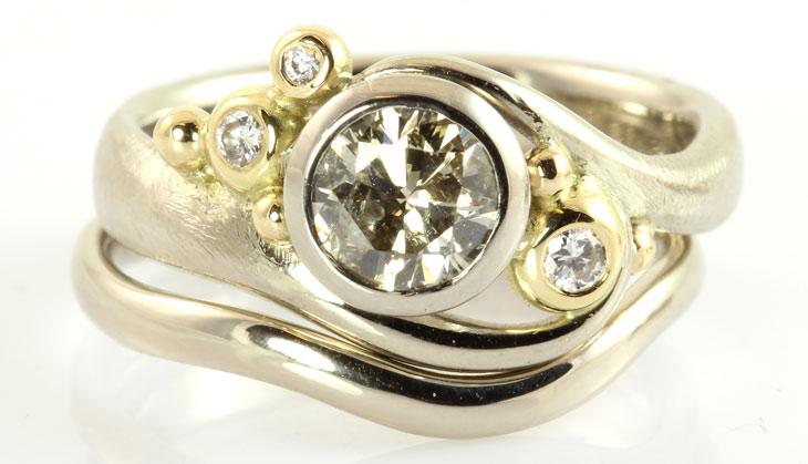 Stor ring med stor diamant i midten og mindre diamanter samt smal ring