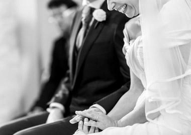 Brudepar der sidder ved siden af hinanden i kirken