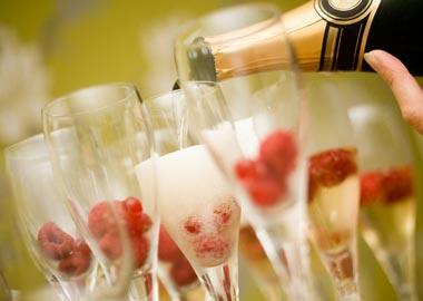 Champagne hældes i glas med frosne bær