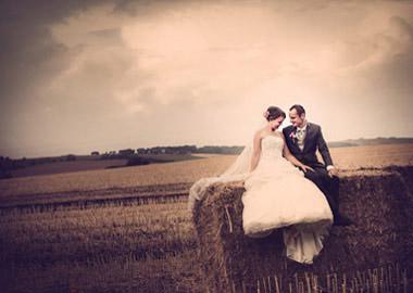 Brudepar der sidder på halmballe