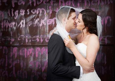 Brudepar der kysser foran en trævæg, der er skrevet på