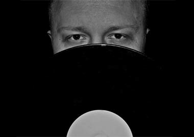 DJ der holder grammofon plade foran ansigtet
