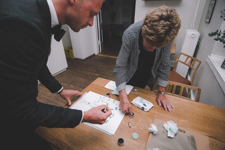 bryllupsgæster sætter fingeraftryk på livets træ