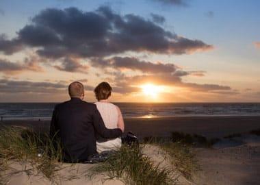 Brudepar i solnedgang på strand