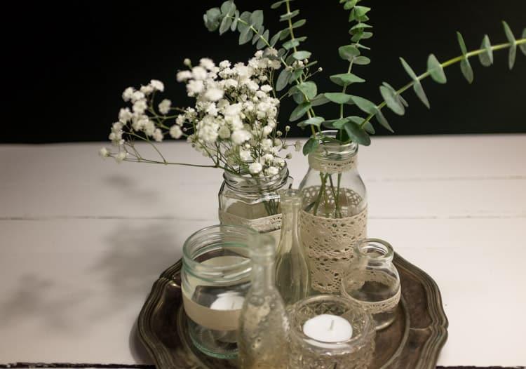 sylteglas med blonder og blomster på sølvfad