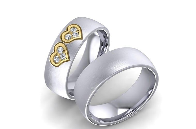 Vielsesringe i rustfri stål, med to hjerter, lavet som en lille forhøjning på dameringen.