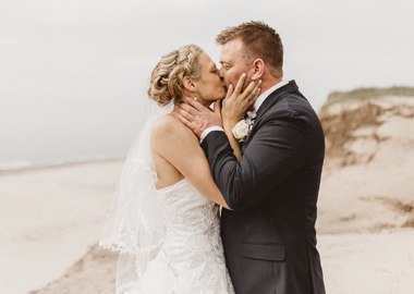 Brudepar kysser ved strand