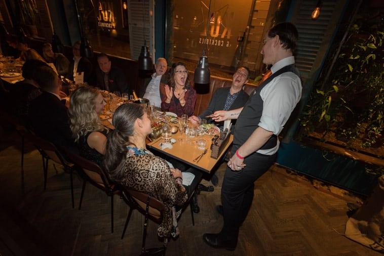Bryllupsgæster underholdes af magiker ved bordet