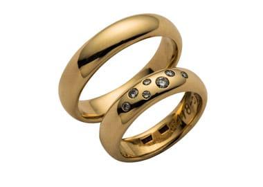 Runde vielsesringe i guld med diamanter i dameringen