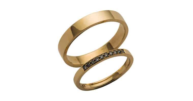Glatte vielsesringe i guld med en række sten i dameringen