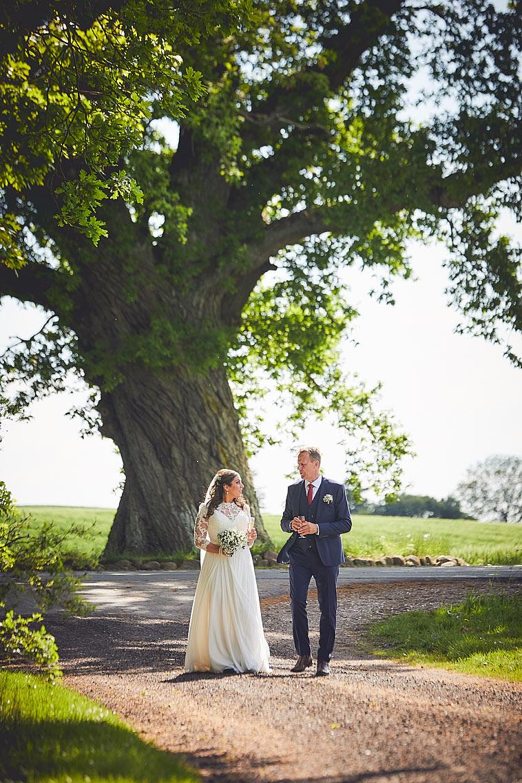 brudepar-foran-stort-træ