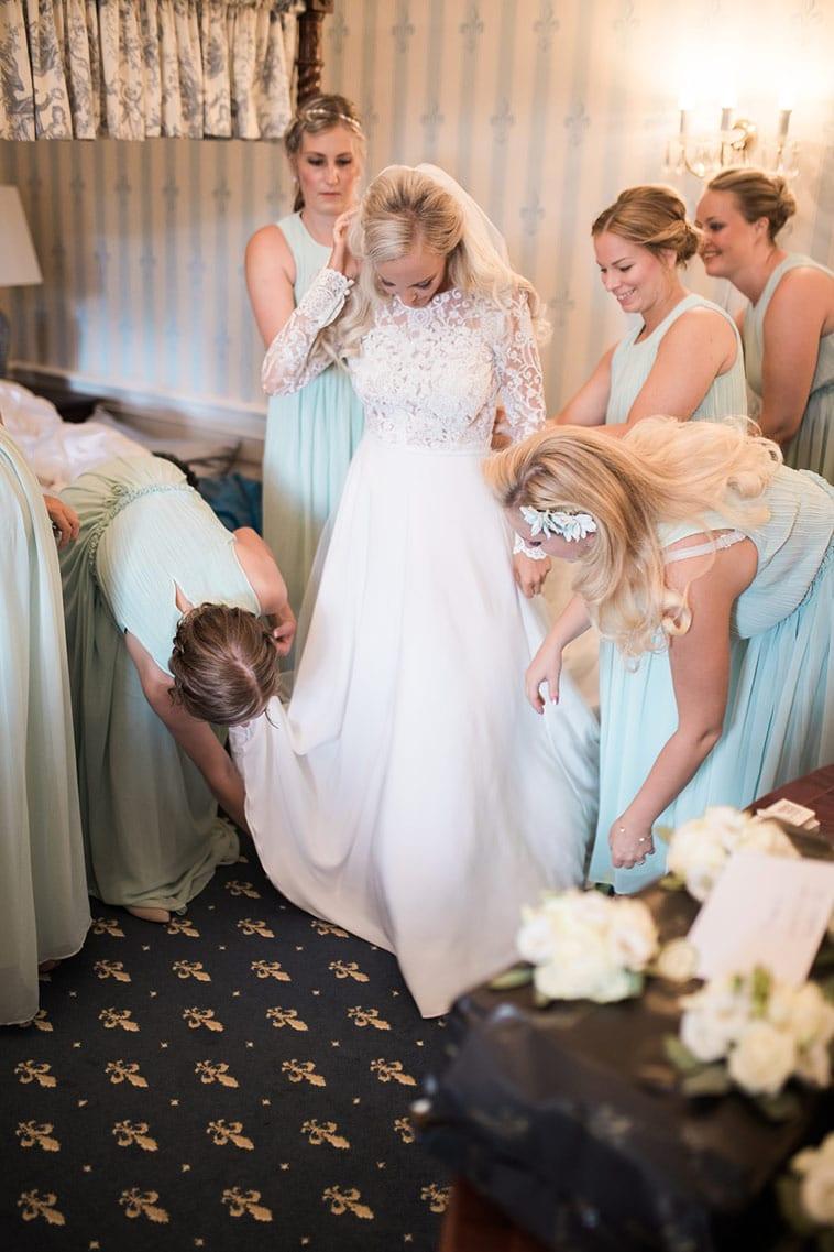 brudepiger hjælper brud med kjolen