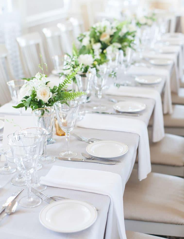 hvidt bryllupsbord med grønne og hvide blomster dekorationer