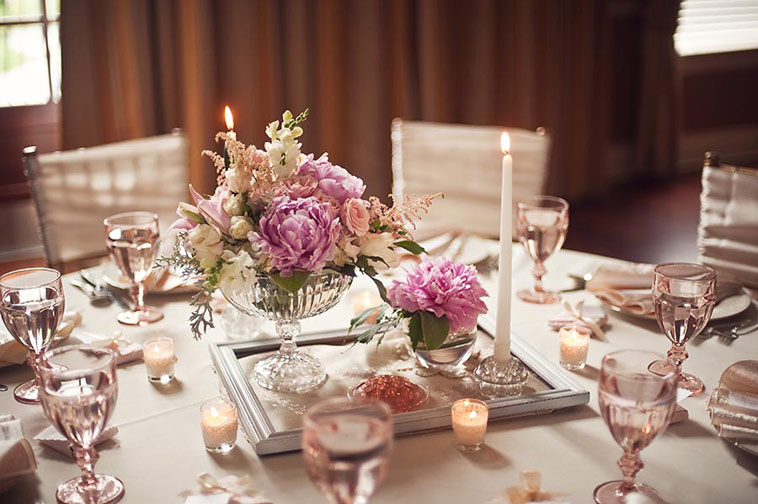 bryllupsbord med blomster i midten i en ramme