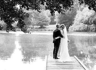 Brudepar der står ved en sø
